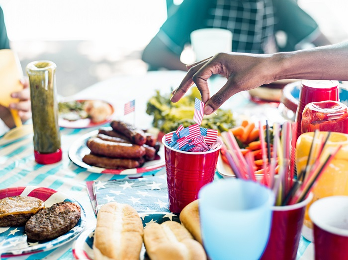 Picnic table with Fourth of July themed decoration and various barbeque food items.