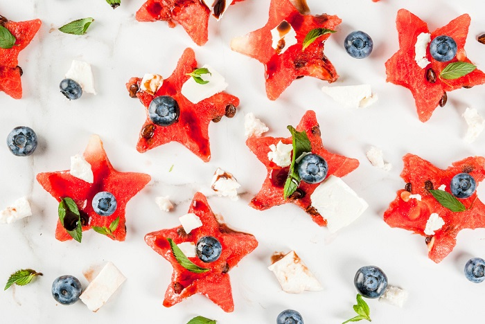 Watermelon sliced in the form of stars, blueberries, feta cheese and balsamic sauce on a white marble table.