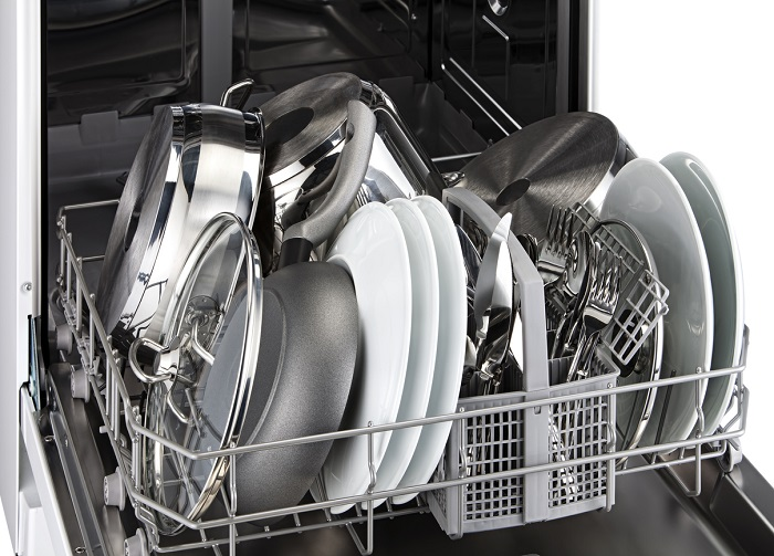 Bottom rack of a dishwasher filled with clean dishes and silverware.