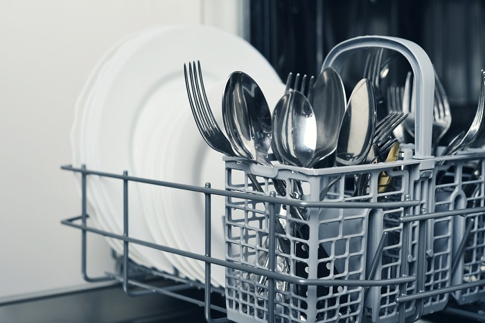 Close up of the bottom rack of a dishwasher that is focused on the clean silverware with white plates in the background.