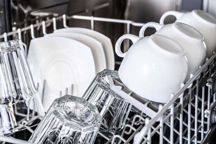 Rows of clean mugs, glasses, and plates loaded up in the top rack of a dishwasher.