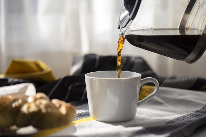 Coffee being poured into cup with breakfast in the background.