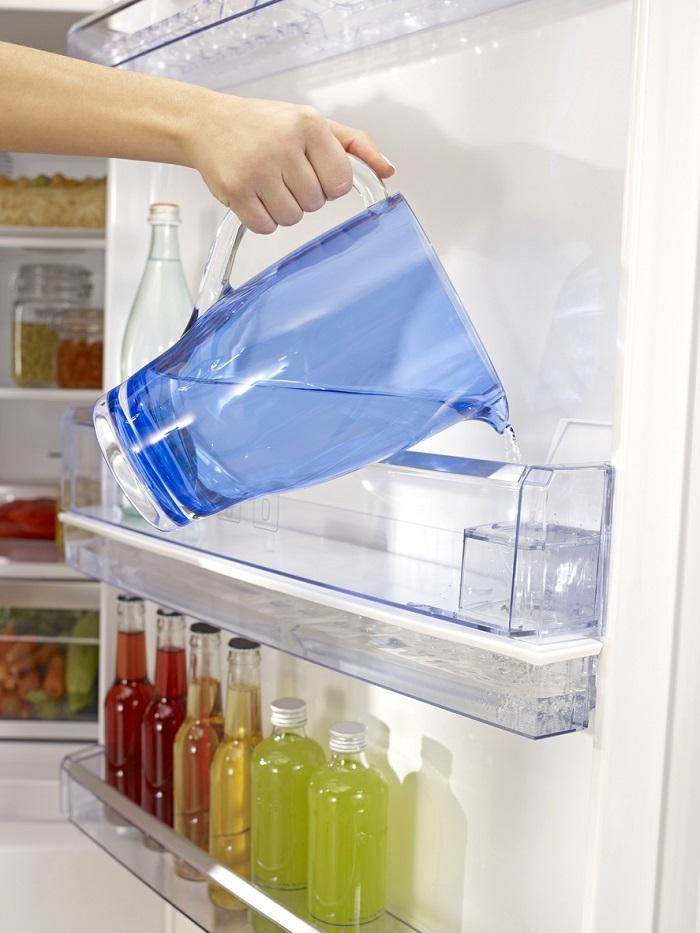 Filling the water tank inside of fridge.