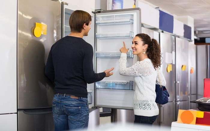 Couple choosing new refrigerator in appliance store.