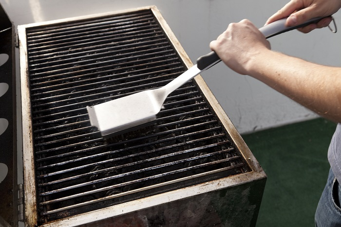 Man cleaning a grill with a grill scrubber.