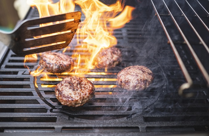 Four burger patties on a fiery grill with visible flames.