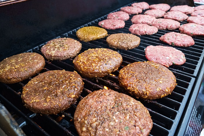 Rows of seasoned burgers on a gas powered grill.