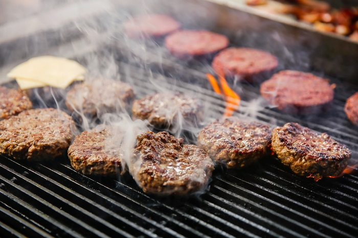Rows of burgers on a fiery grill with visible smoke.