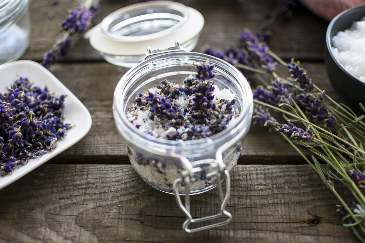 Jar filled with bath salts and lavender with lavender flowers on each side.