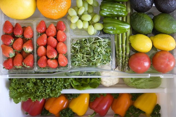 Crisper drawer of fridge filled with fruits and vegetables.