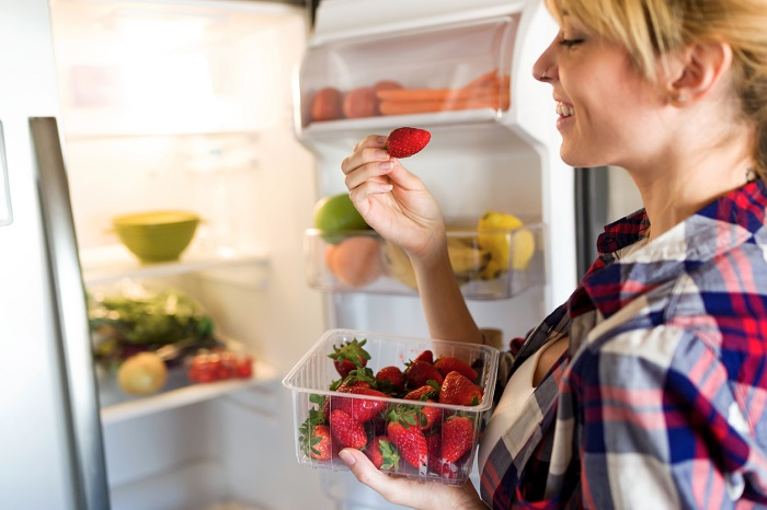 Young woman pulling strawberries out of the fridge.