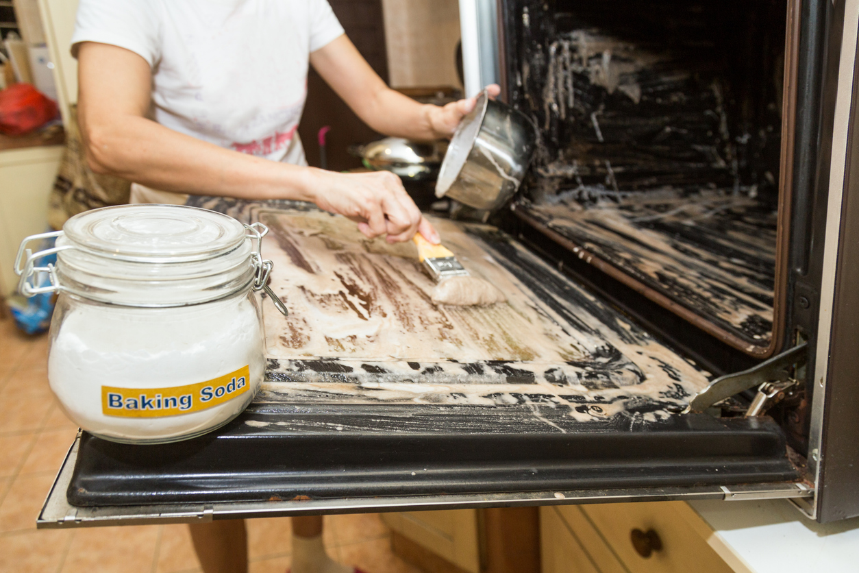 person smearing baking soda paste into their oven for cleaning