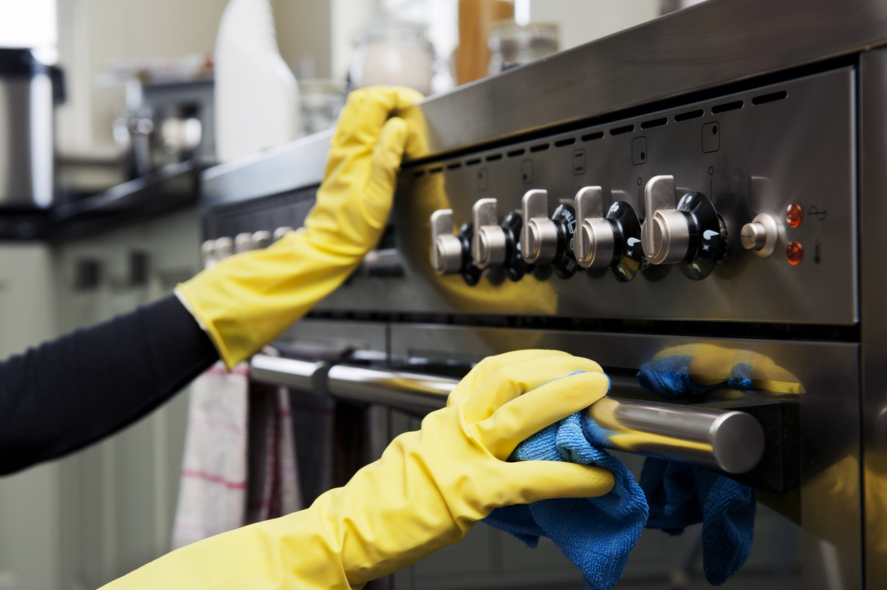 two hands cleaning a black oven range in a domestic kitchen