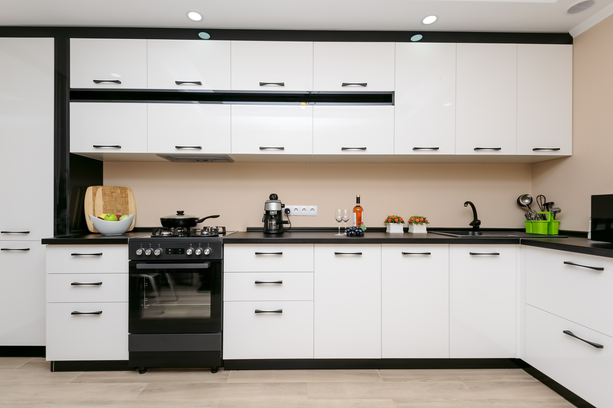 modern spacious kitchen with black range and white cabinetry