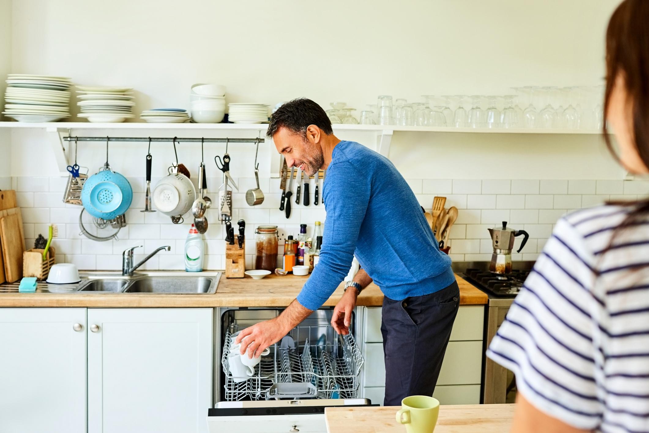 man loading coffee mugs into the dishwasher