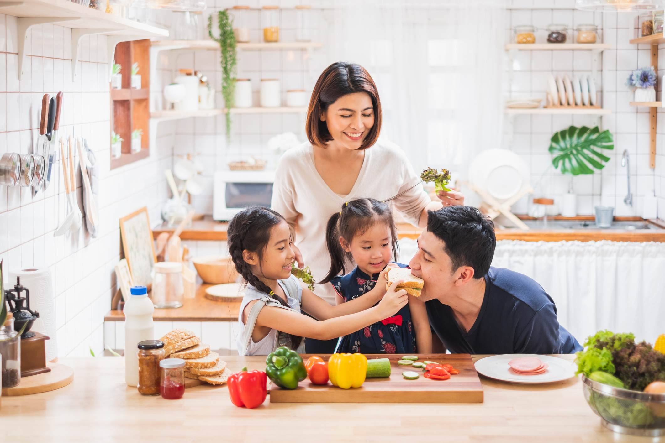 family making sandwiches and feeding their parents