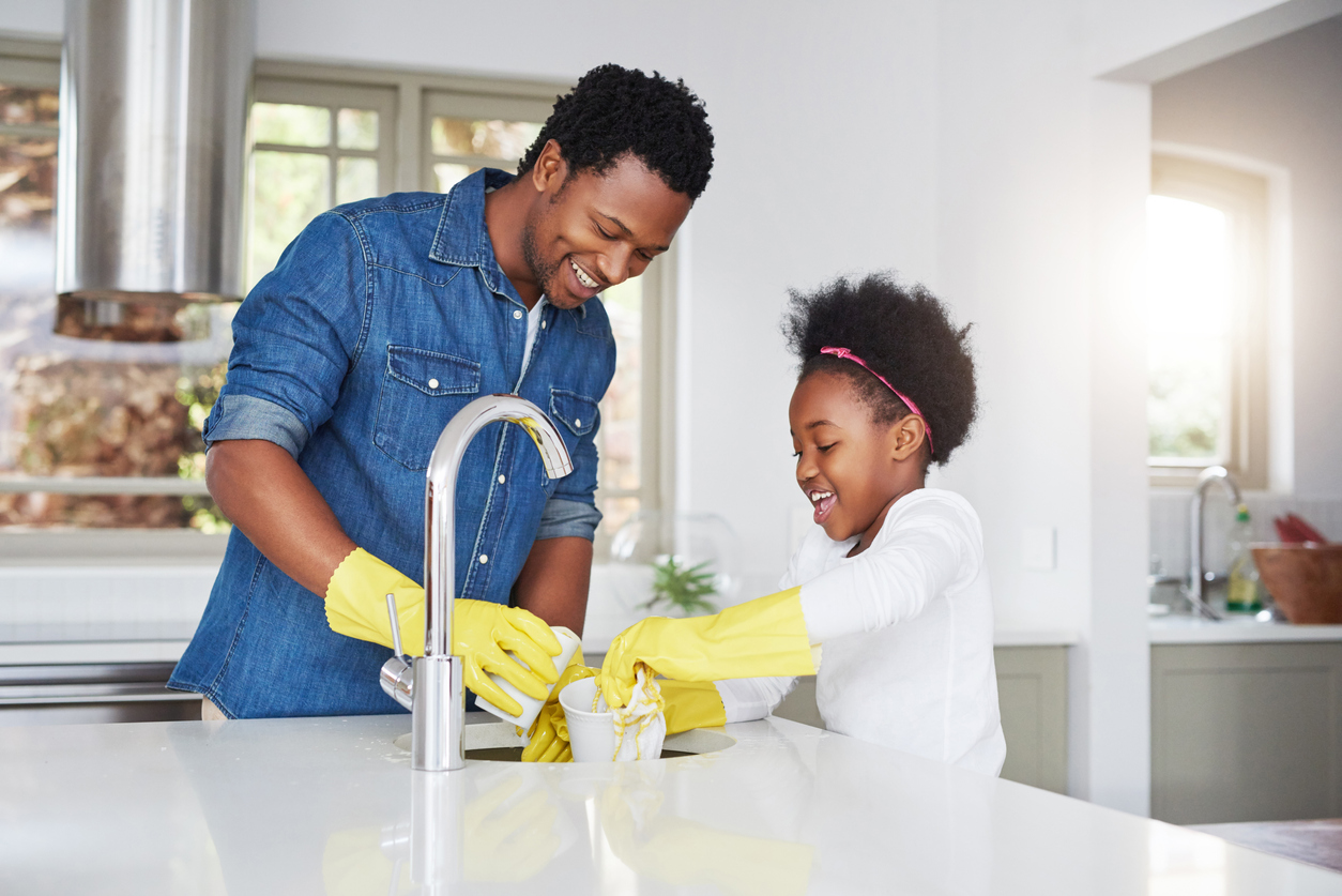 little girl and her father enjoying the kitchen cleanup at home