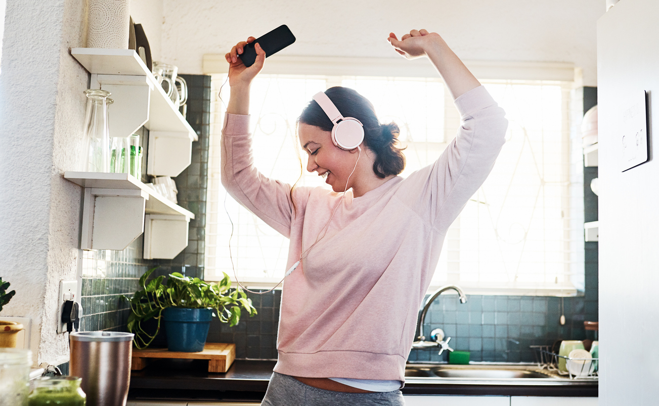 young woman listening to music through her headphones in the kitchen