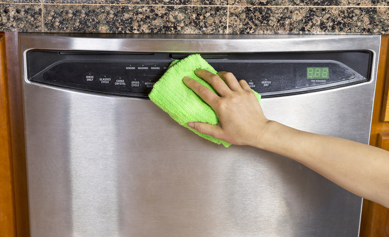 person cleaning a stainless steel dishwasher with a green microfiber cloth