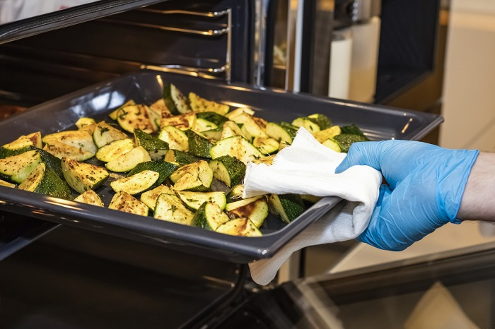 Cook takes out from the oven a sheet of the tray with fried zucchini.