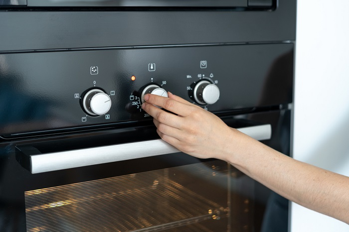 Hand adjusting the temperature knob on the oven.