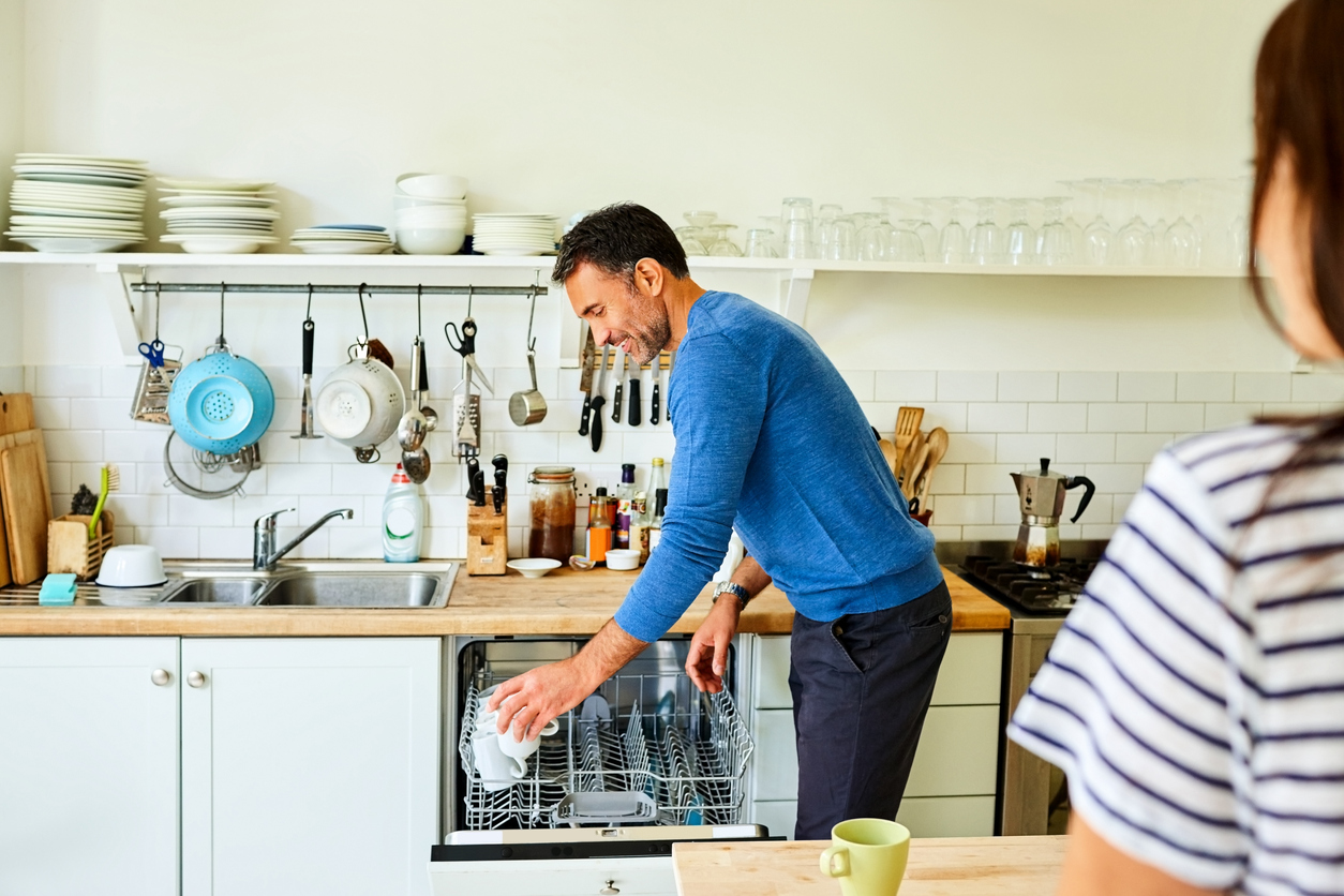 man putting coffee mugs in dishwasher