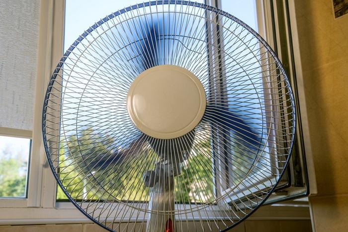 Fan is running near an open window.