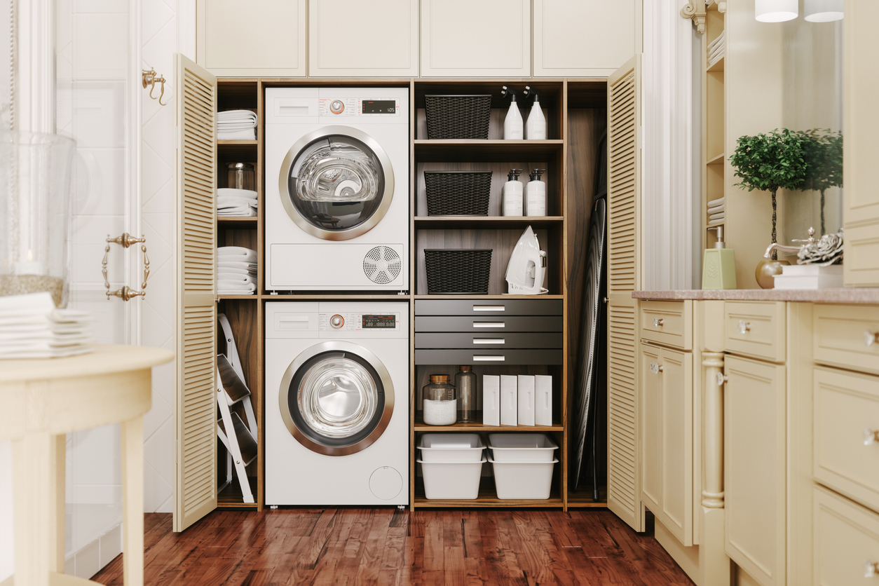 open freestanding closet revealing stackable washer and dryer and other laundry accessories