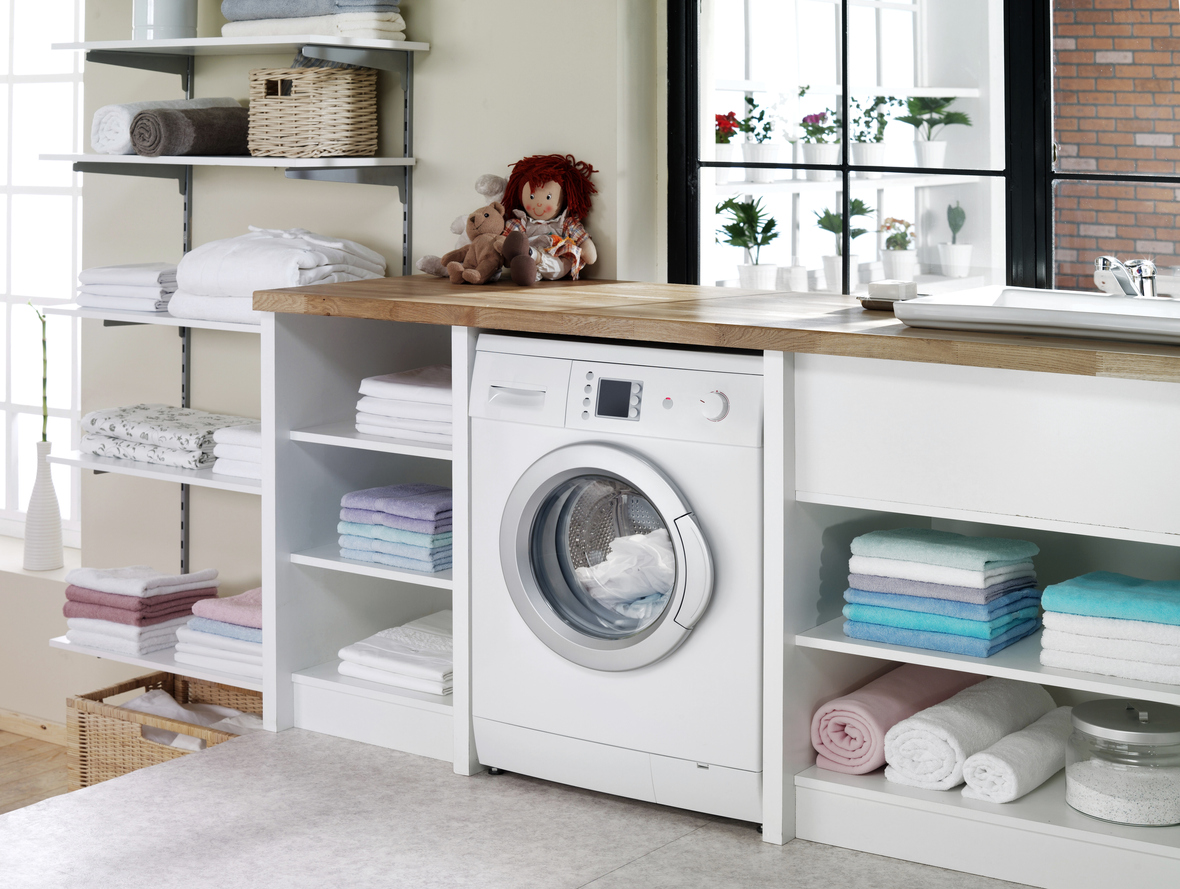 streamlined laundry room featuring a cabinet with open shelves