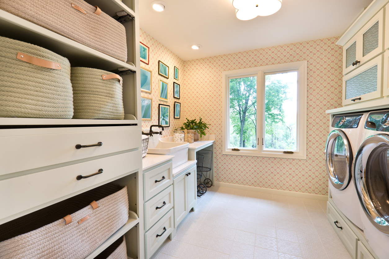 modern laundry room with cabinet and storage bins