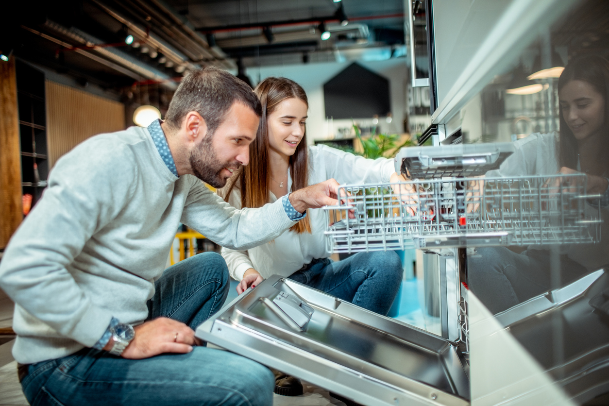 man and woman crouch to inspect new dishwasher