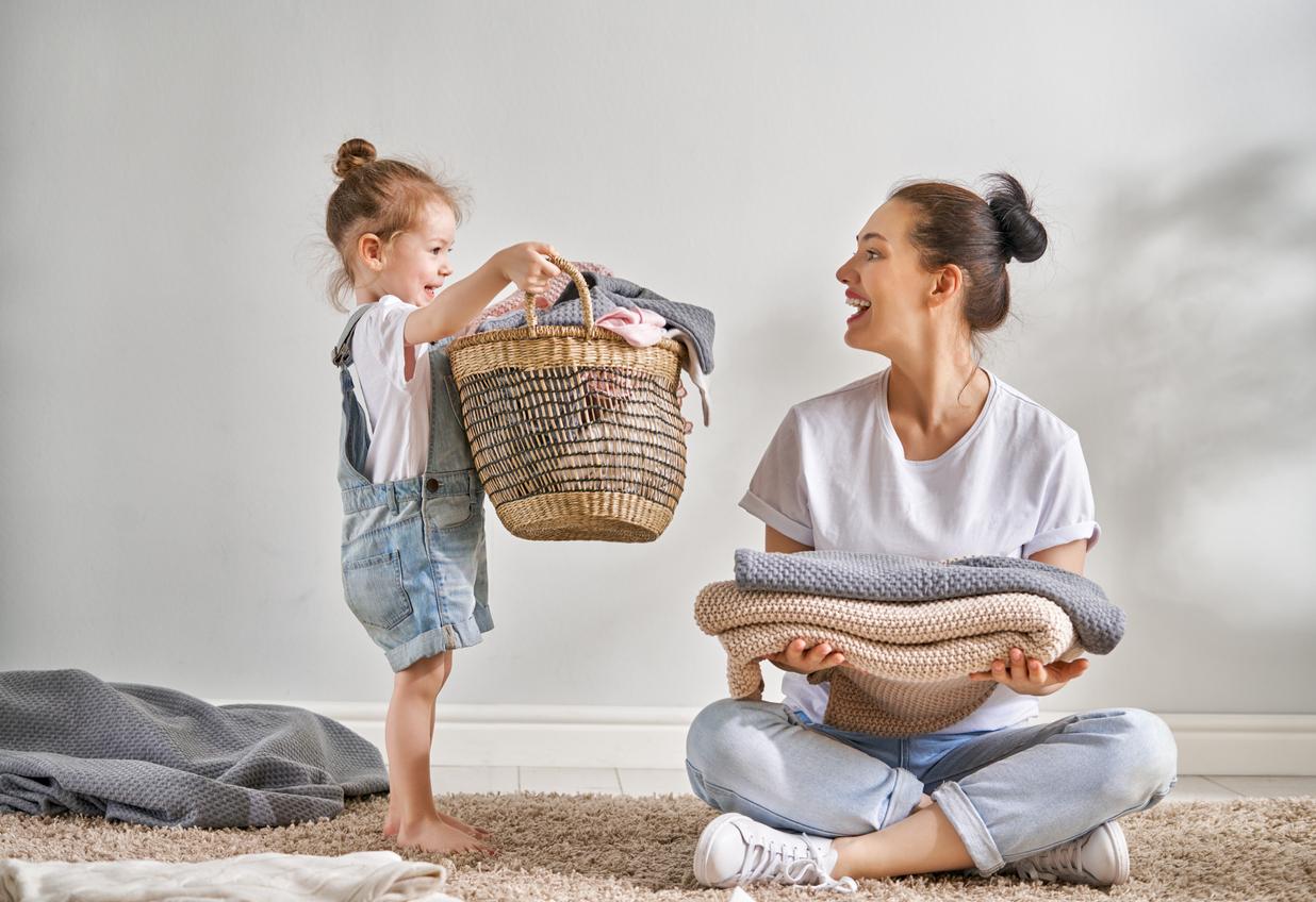mother sitting cross-legged holding folded sweatshirts smiles at daughter holding laundry basket