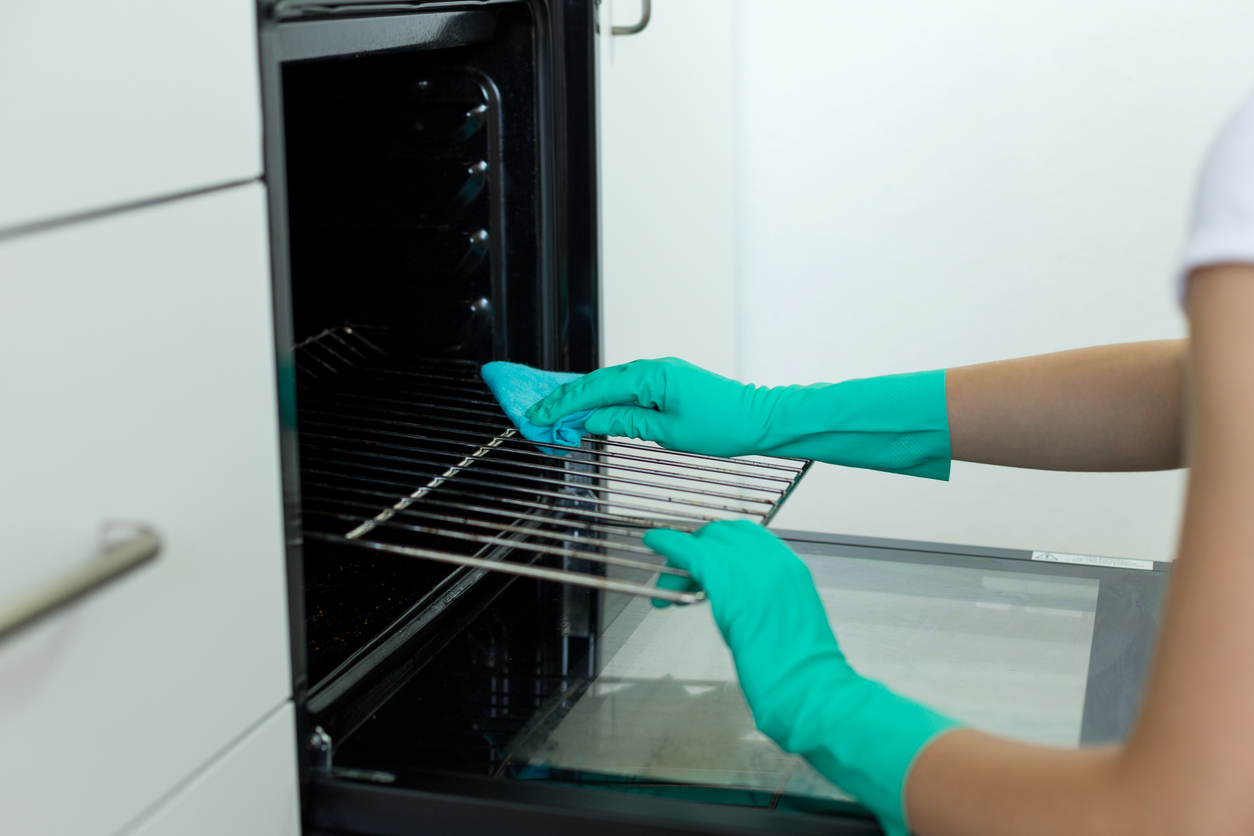 person in rubber gloves cleaning their oven racks