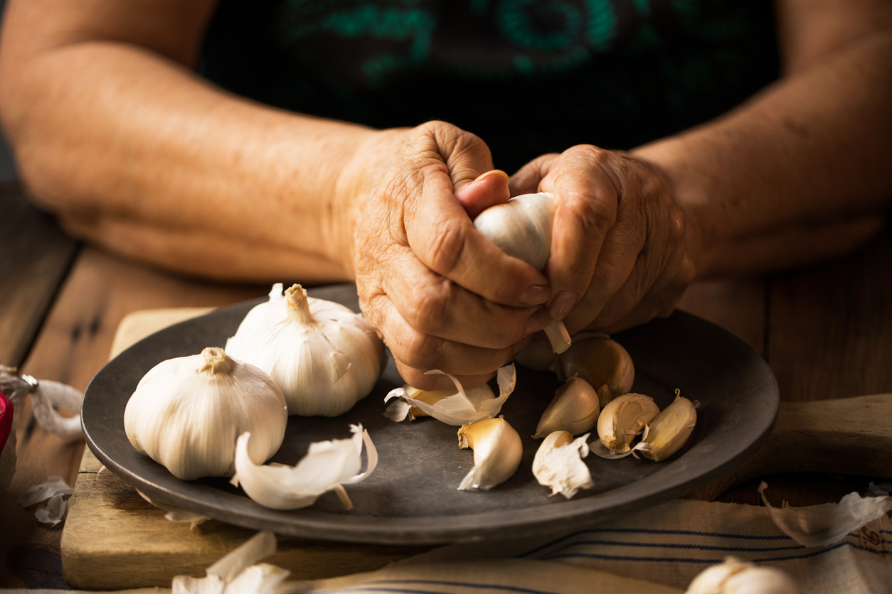 close-up of a woman's hands removing garlic skin over a plate