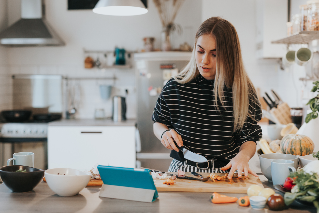 Young woman cooks using a recipe management app