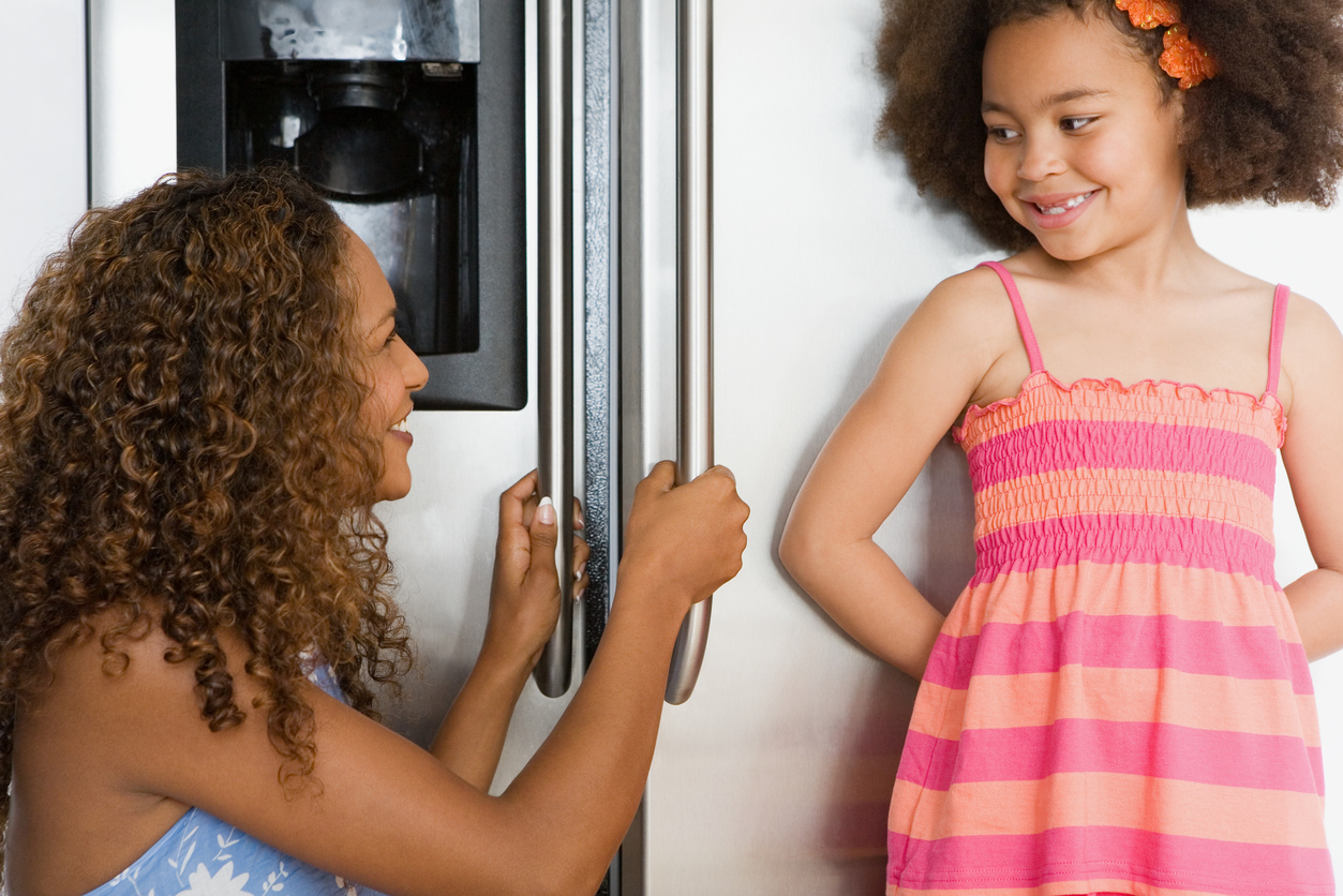 girl and mother in front of side by side refrigerator