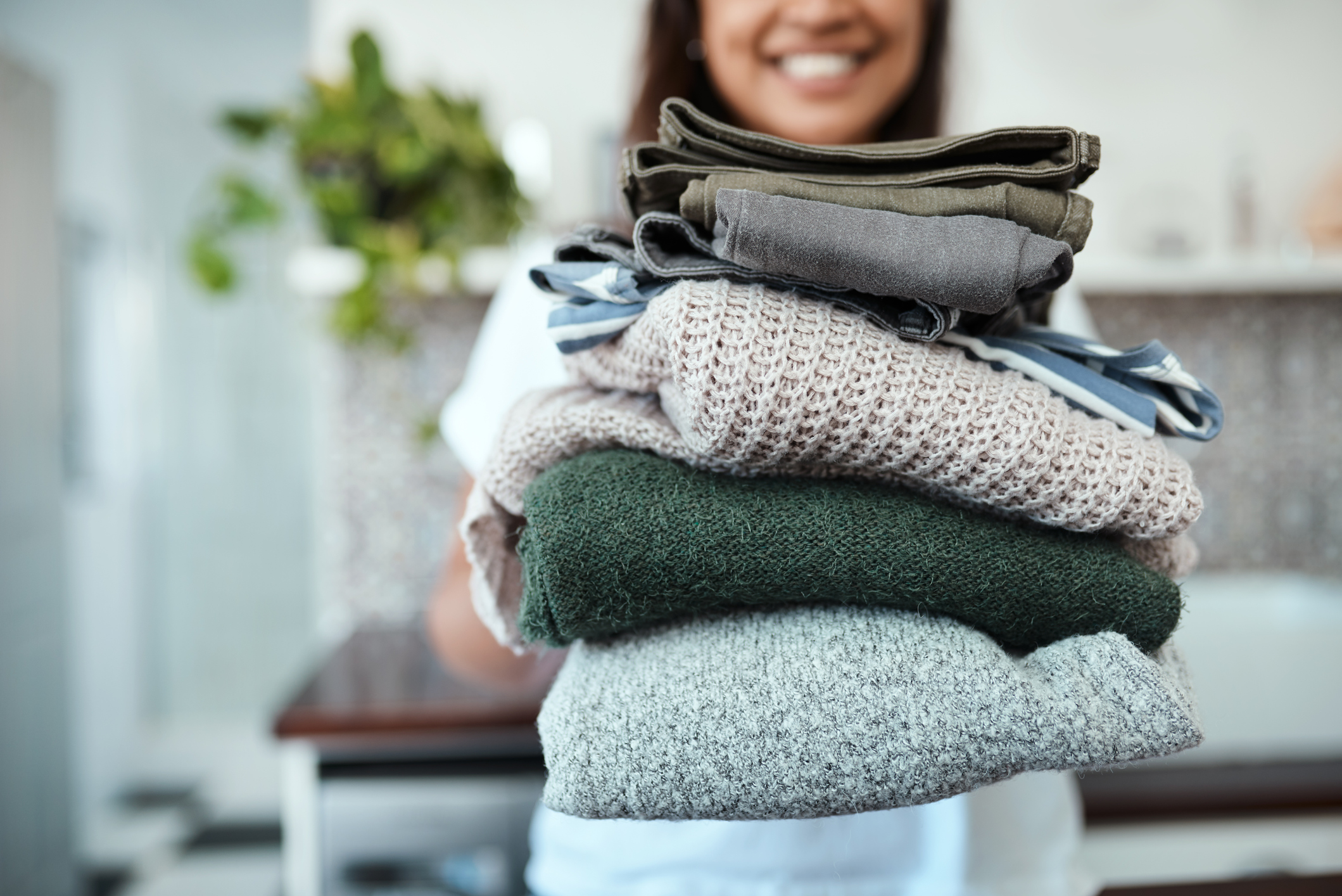 woman holding a stack of clean laundry