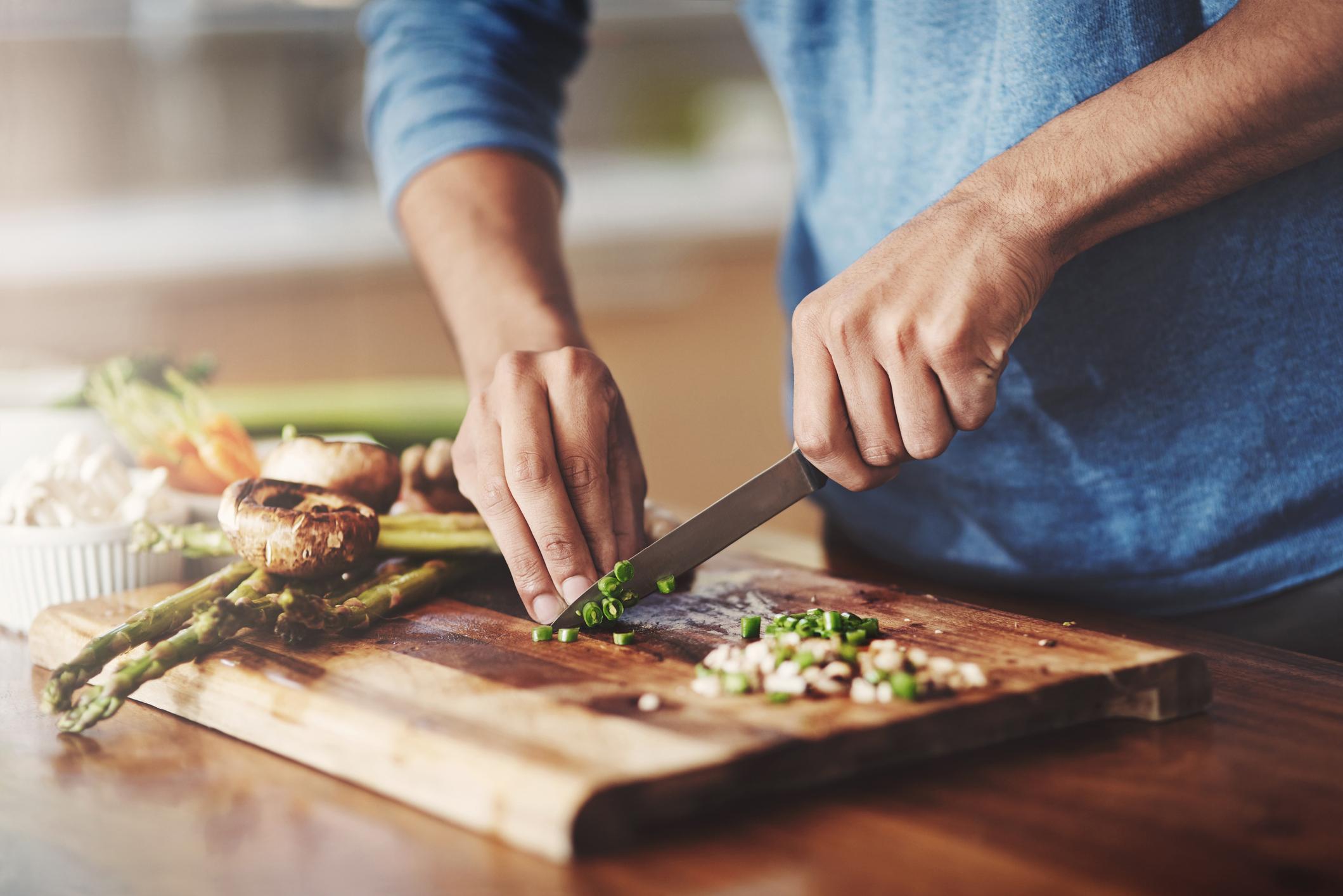 man slicing veggies for dinner