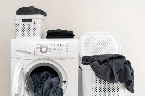 White washing machine with blanket in drum and blankets of laundry around it