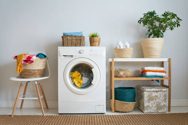 small washer with a load of laundry inside and a clothes basket beside it