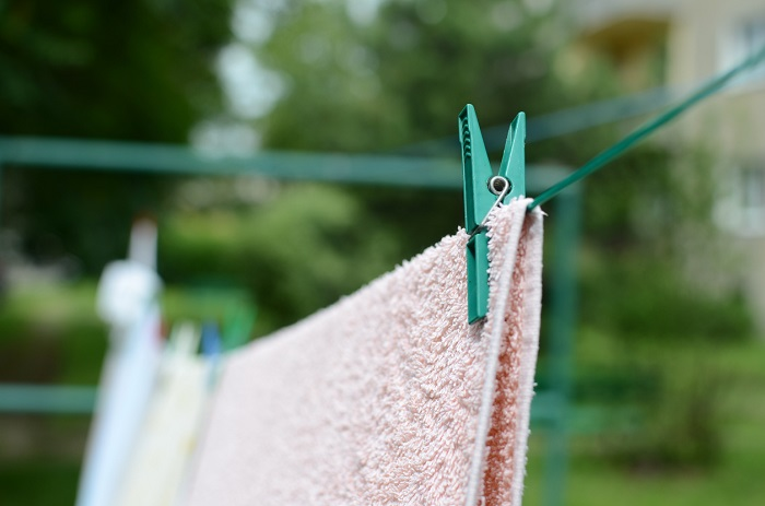 Hanging towel outdoors on a clothes line.