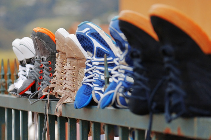 Running shoes drying on a fence.