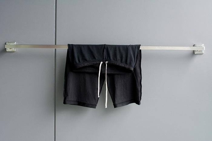 Swimming suit hanging on rack in bathroom.