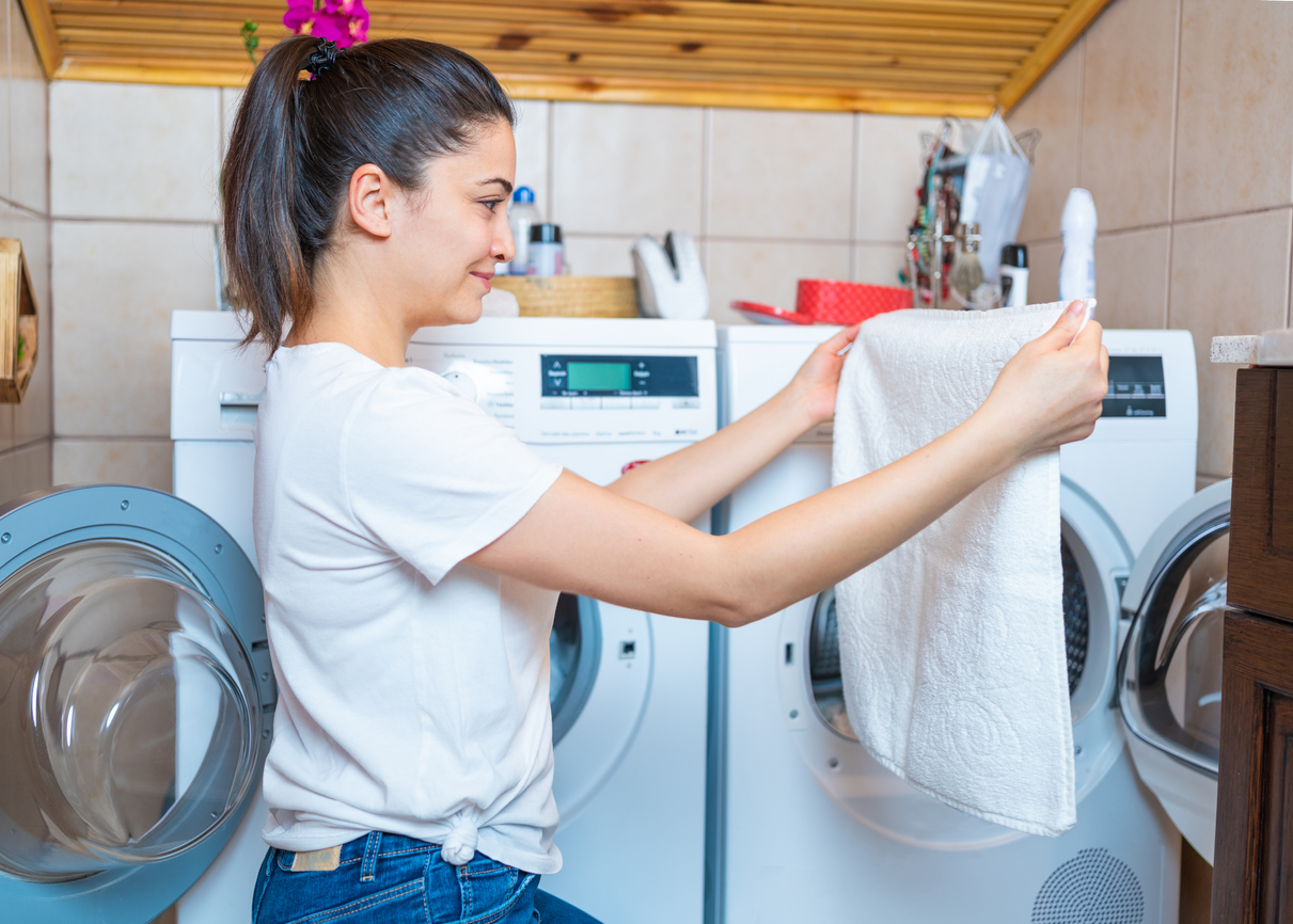 woman smiles as she takes clothes out of front-loading washer