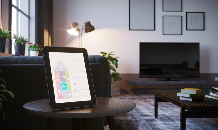 A modern living room with a tablet turned on and sitting on a table.