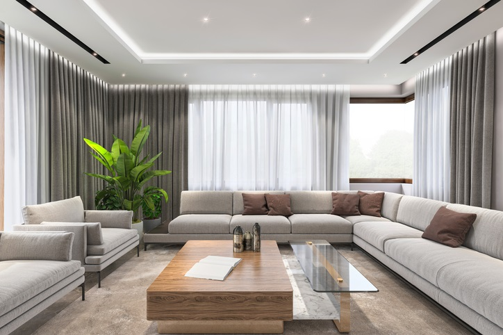 Modern villa interior, large sofa and armchairs, coffee table and lot of sunlight