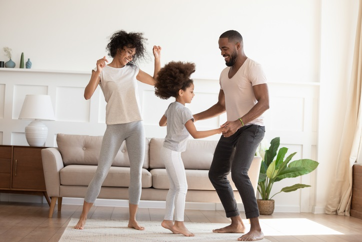 Two parents dance with their daughter at home