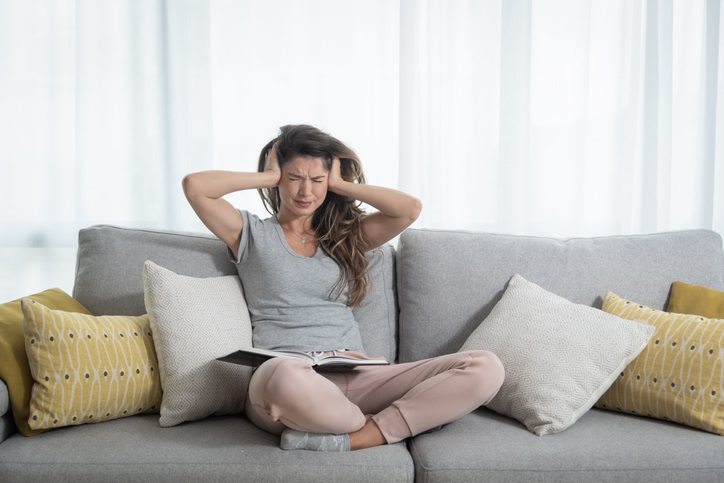 Woman blocks her ears at home on her couch