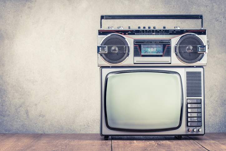 Retro old TV set receiver and radio cassette recorder on table front textured concrete wall background.