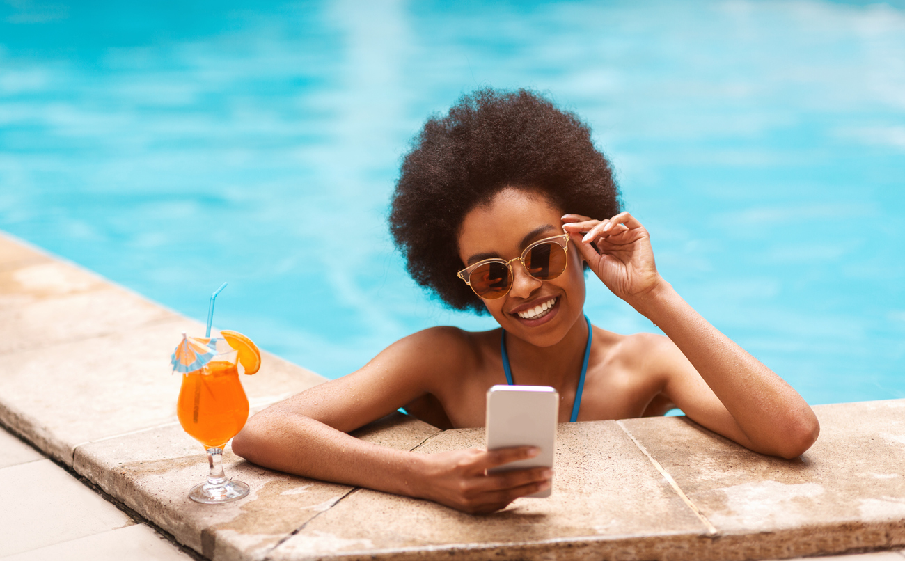 woman lounging by the pool with her smartphone